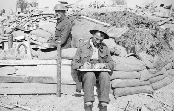 WWI soldier writing a letter as a second soldier looks at the camera from the background
